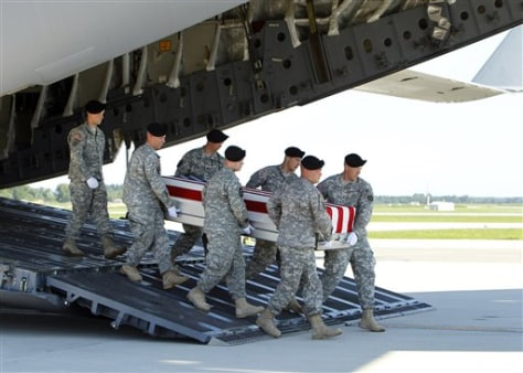 An Army carry team moves a transfer case containing the remains of Spc. Michael C. Roberts