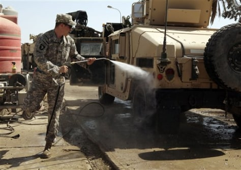 Image: Army soldier washes a Humvee