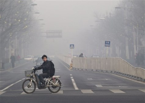 Image: A man rides a bike across a street shrouded by haze in Beijing