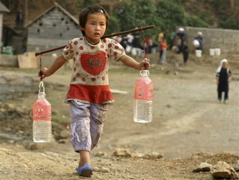 Image: Girl carries water bottles