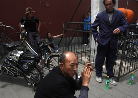 Image: Men smoke on a street in Beijing