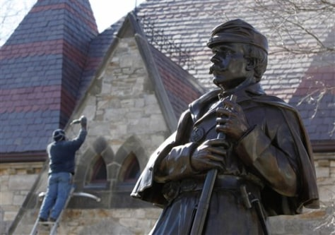 Image: A workman does repairs at the Framingham History Center behind a statue of a Union soldier in Framingham, Mass.