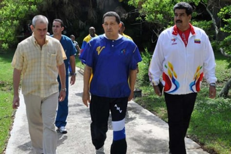 Image: Venezuela's President Hugo Chavez, center, walks with his Foreign Minister Nicolas Maduro, right, and an unidentified person