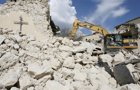 Image: Excavator digs through the rubble