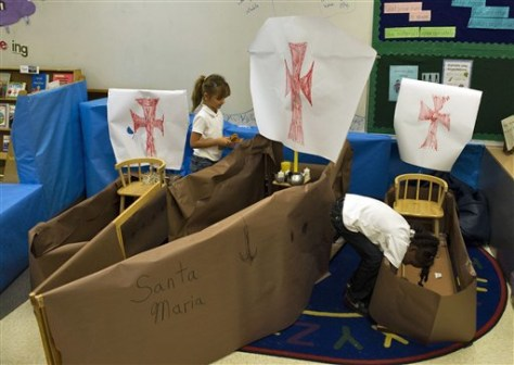 Image: Kindergarten students Kaileen Barreto, left, and Shayonna Bridgeman load supplies into paper ship replicas