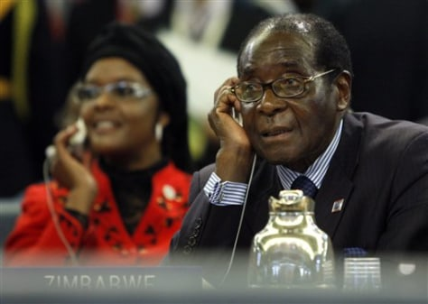 Image: Zimbabwean President Robert Mugabe, foreground right, listens to his ear piece as his wife Grace is seen in the background