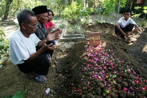 IMAGE: Relatives pray at grave