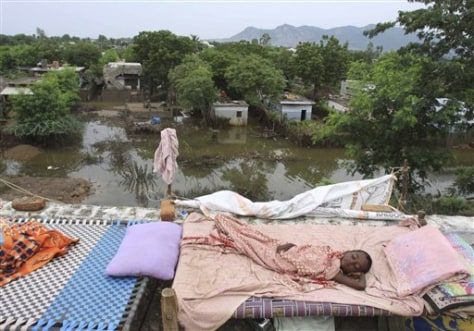 Image: Boy rests in flooded area