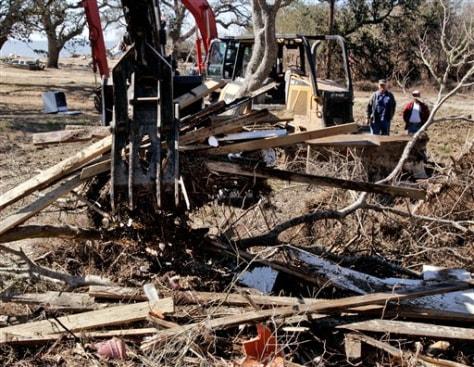Image: Backhoe lifts debris