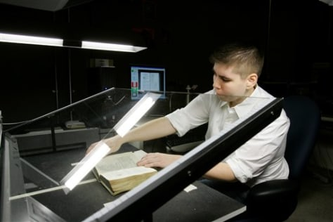 Image: Courtney Mitchel helps a giant desktop machine digest a rare, centuries-old Bible.