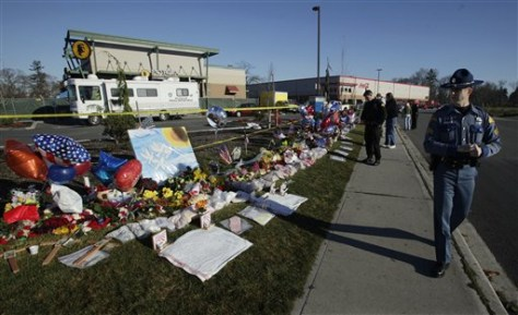 Image: Washington State Patrol Sgt. Keith Trowbridge, right, visits the memorial at the Forza Coffee Company