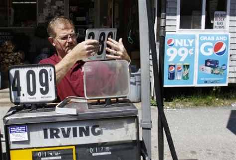 Image: Convenience story owner Floyd Bisson, lowers the price of regular gas at the pumps in front of his store in Phippsburg, Maine on Monday.