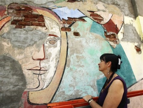"Image: Arnold Belkin's widow Patricia Quijano Ferrer studies damage to a detail of Belkin's 1972 public mural ""Against Domestic Colonialism"""