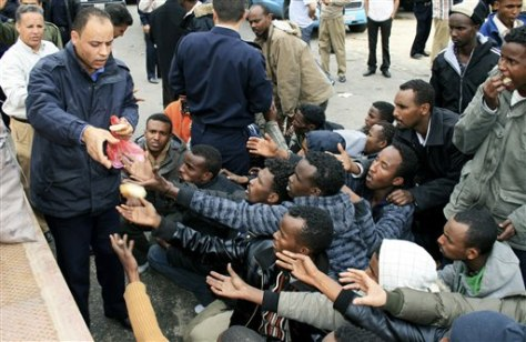 Image: Police hand out bread to migrant survivors