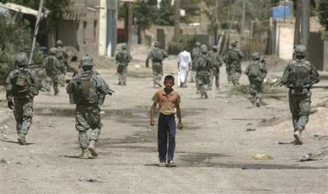 Image: Boy walks down street as U.S. soldier patrol