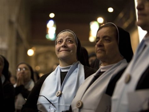Image: Catholic nuns look up at a poster of Maria Alfonsina Danil Ghattas
