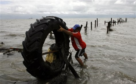 Image: Man pulls tire out of water