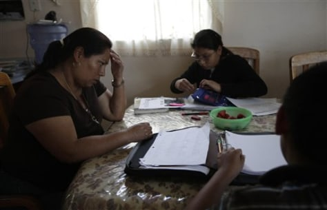 Image; Domitila Lara, left, helps her children Ariana, center, and Eduardo, right, with their homework