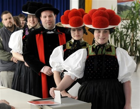 Image: Tanja Lauble, Christine Haas, Mike Lauble und Melanie Haas in traditional Black Forest clothes, line up to cast their ballots in Gutach, southern Germany on Sunday