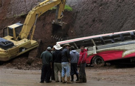 Image: People stand in front of a bus partially covered by a landslide