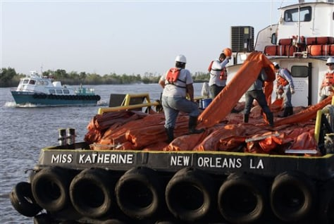 Image: Workers load oil booms