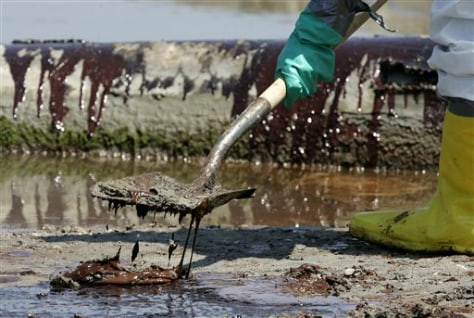 Image: A worker shovels oil from the Deepwater Horizon oil spill