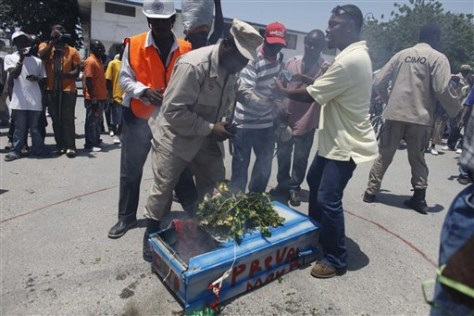 Image: Police try to prevent demonstrators in Haiti from burning a symbolic coffin