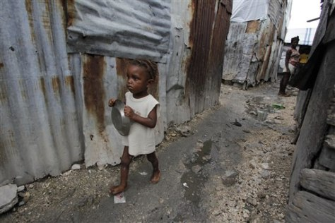 Girl with tin plate in Port-au-Prince, Haiti.