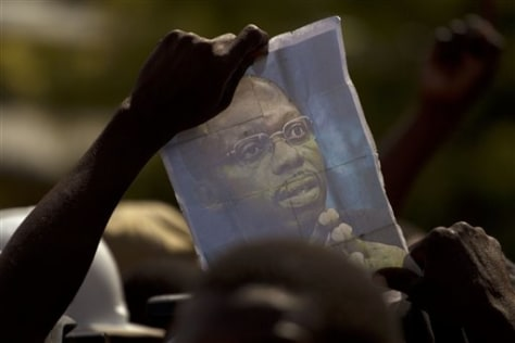 Image: A demonstrator holds up a picture of ousted Haitian President Jean-Bertrand Aristide