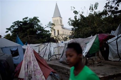 Image: A young grild walks next to tents