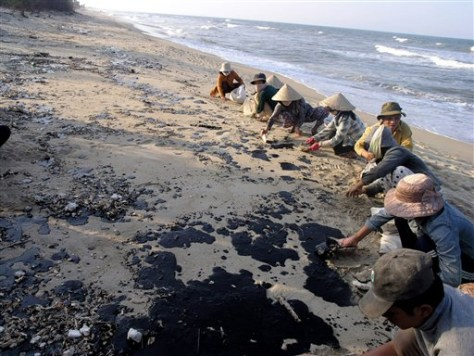 IMAGE: VILLAGERS CLEAN OIL OFF BEACH