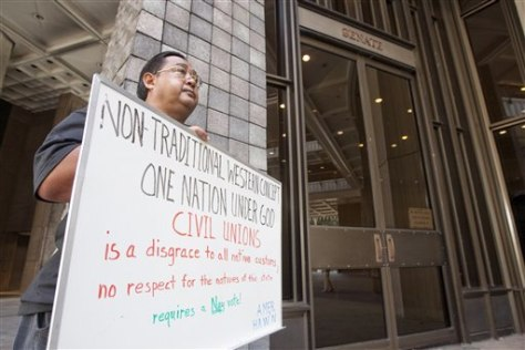 Image: Enrick Ortiz of Kahaluu holds a sign outside the Hawaii State Senate Chambers