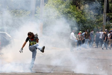 Image: A demonstrator kicks at a cloud of tear gas