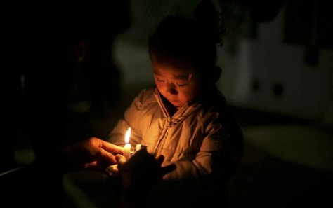 Image: A young Tibetan girl participates in a candlelit vigil