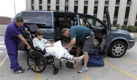 Image: Tim Brunn of Island Lake, Ill., helps his son, Josh, into their van after he was released from the hospital