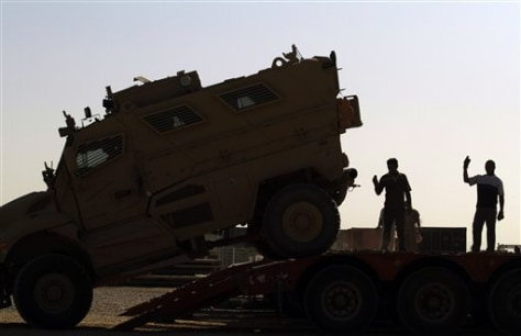 Image: Iraqi truck drivers help guide vehicle onto flatbed truck