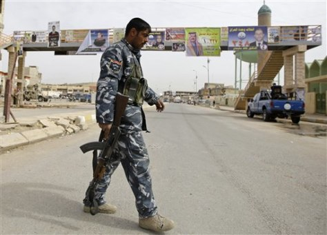 Image: Iraqi policeman walks past campaign posters