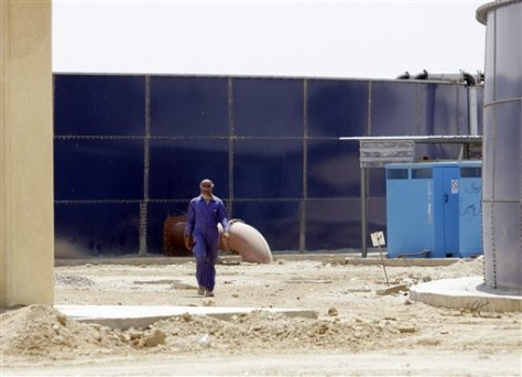 Image: A worker walks through the nearly-complete waste water treatment site in Fallujah