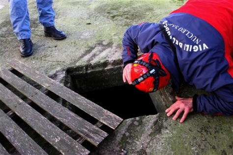 Image: A firefighter looks inside a hole Monday for missing twins