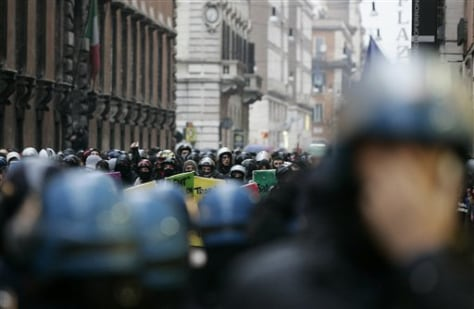 Image: Demonstrators wear helmets in a face-off against police