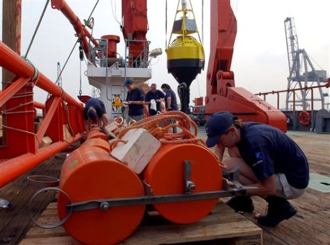 Crew member installs equipment on buoys