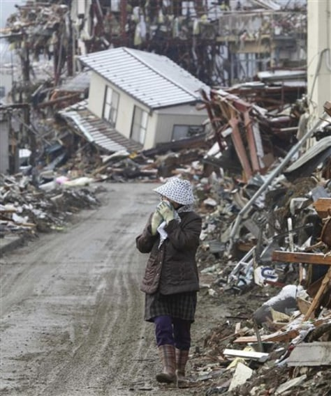 Image: Woman walks through debris looking for household belongings