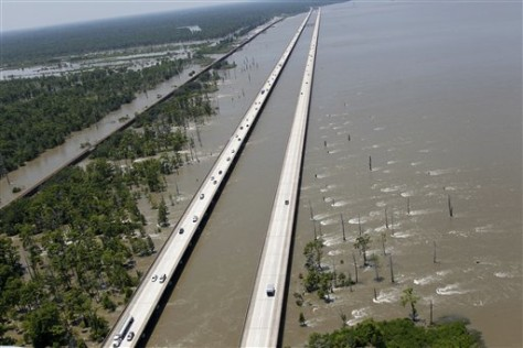 Image: Cars travel along Interstate 10 while water from the Mississippi River is seen rushing from left to right through the Bonnet Carre Spillway into Lake Pontchartrain near Norco, La.