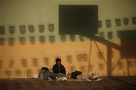 Image: Migrants rest at a temporary shelter