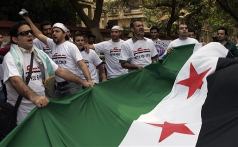 Image: Men hold a Syrian national flag