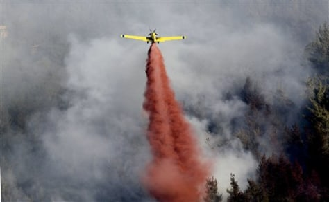 Image: A plane drops red fire retardant