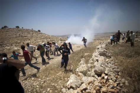 Image: Palestinians run from tear gas fired by Israeli soldiers during a demonstration against the expansion of nearby settlements at the West Bank village of Dier Qadis, near Ramallah.