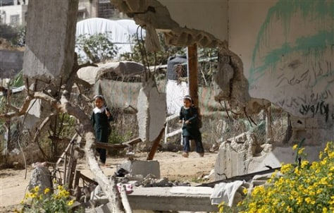 Image: Palestinian girls walk past a house