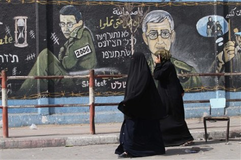 Image: Palestinians walk in front of wall painting showing captive Israeli army soldier Sgt. Gilad Schalit.