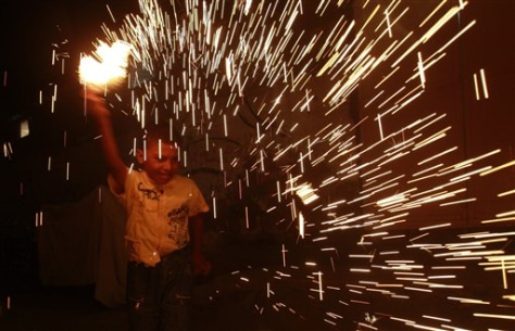 Image: Palestinian child plays with fireworks on the first day of Ramadan